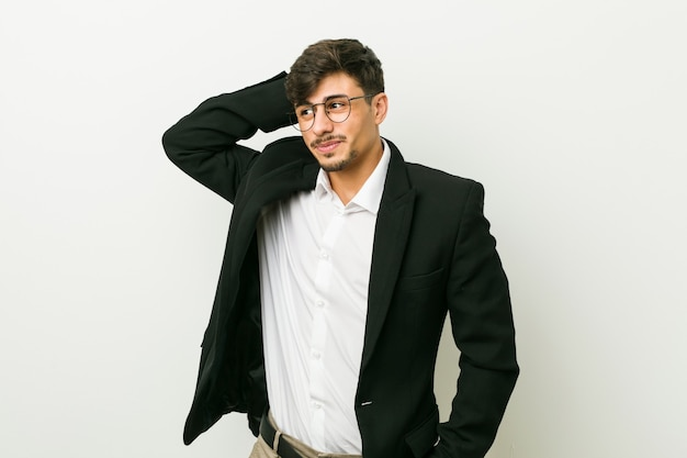Jeune homme hispanique d'affaires touchant l'arrière de la tête, pensant et faisant un choix.