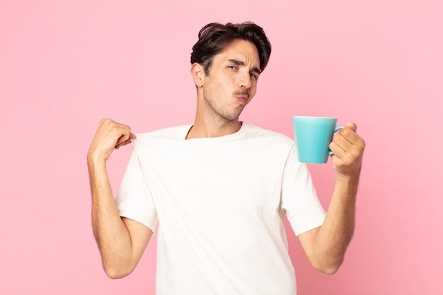 Jeune homme hispanique à l'air arrogant, réussi, positif et fier et tenant une tasse de café
