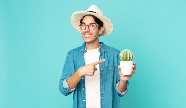 Jeune homme hispanique à l'air excité et surpris pointant sur le côté et tenant un cactus