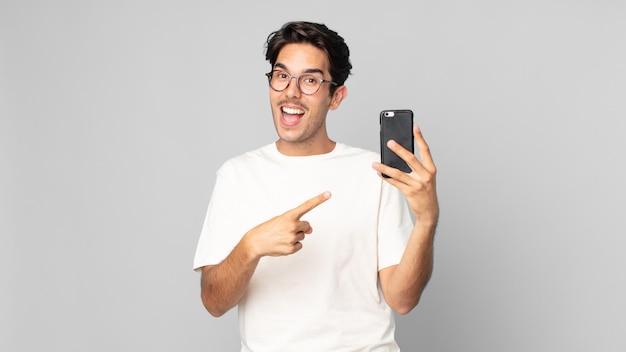 Jeune homme hispanique à l'air excité et surpris pointant sur le côté et tenant un smartphone