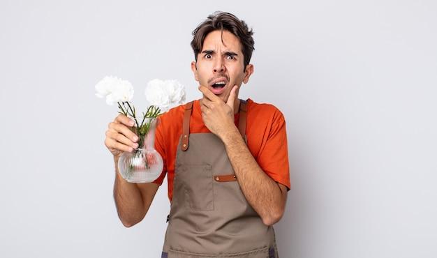 Jeune homme hispanique avec la bouche et les yeux grands ouverts et la main sur le menton. concept de fleuriste