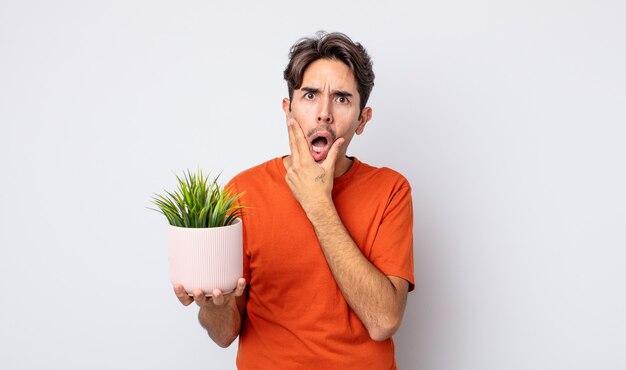 Jeune homme hispanique avec la bouche et les yeux grands ouverts et la main sur le menton. concept de plante décorative