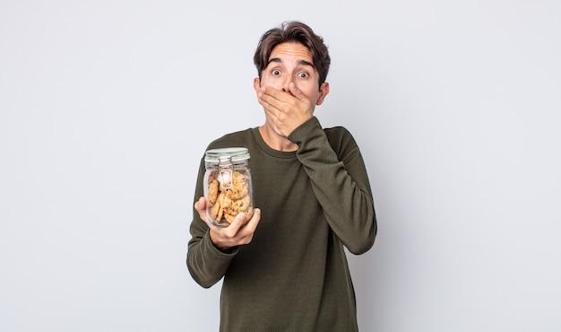 Jeune homme hispanique couvrant la bouche avec les mains avec un choc. notion de cookies