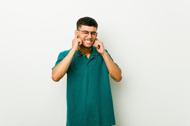 Jeune homme hispanique couvrant les oreilles avec les mains