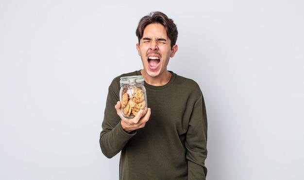 Jeune homme hispanique criant agressivement, l'air très en colère. notion de cookies