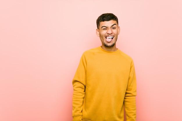 Jeune homme hispanique drôle et sympathique qui tire la langue.