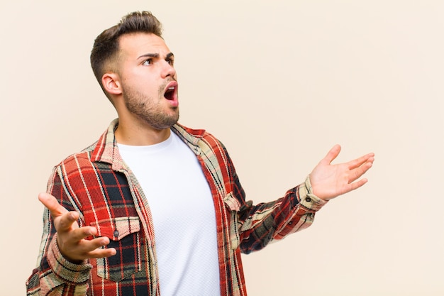 Jeune homme hispanique effectuant un opéra ou chantant lors d'un concert ou d'un spectacle, se sentant romantique, artistique et passionné contre un mur isolé