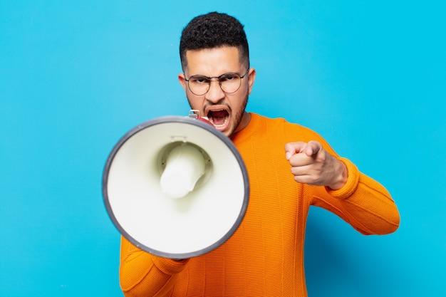 Jeune homme hispanique expression en colère et tenant un mégaphone