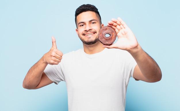 Jeune homme hispanique expression heureuse et tenant un beignet