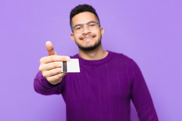 Jeune homme hispanique expression heureuse et tenant une carte de crédit