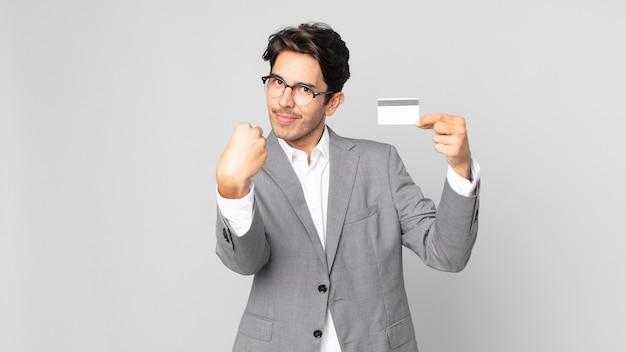 Jeune homme hispanique faisant un geste de capice ou d'argent, vous disant de payer et tenant une carte de crédit