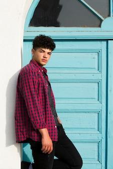 Jeune homme hispanique frisé se penchant sur le mur près de la porte