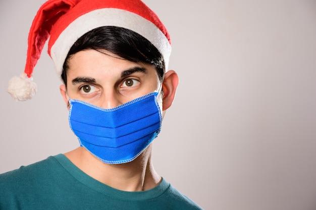 Jeune homme hispanique avec un masque facial et un bonnet de noel à côté
