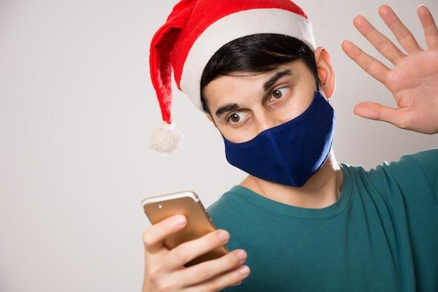 Jeune homme hispanique avec un masque facial et une salutation de bonnet de noel tout en faisant un appel vidéo