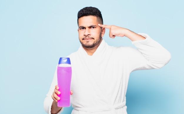 Jeune homme hispanique pensant à l'expression et portant un peignoir