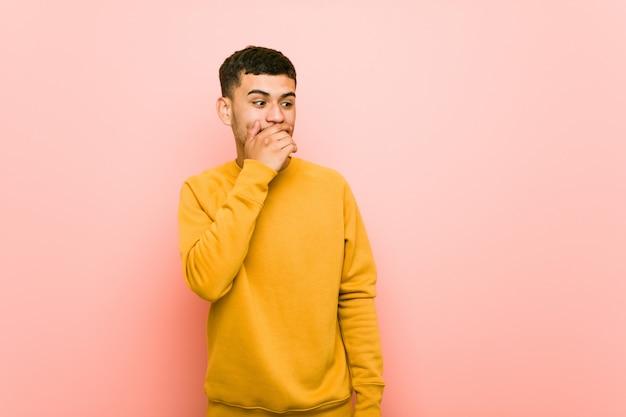 Jeune homme hispanique pensif à la recherche d'un espace copie couvrant la bouche avec la main.