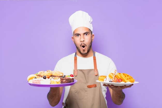 Jeune homme hispanique peur de l'expression. chef avec concept de gaufres