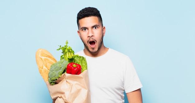 Jeune homme hispanique peur de l'expression. concept d'achat de légumes