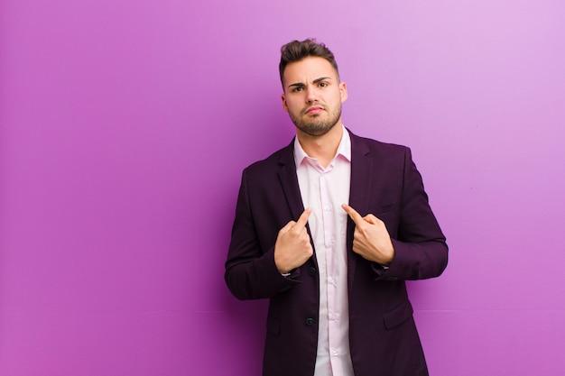 Jeune homme hispanique pointant sur lui-même avec un regard confus et interrogateur, choqué et surpris d'être choisi