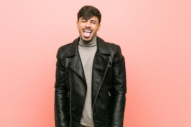 Jeune homme hispanique portant une veste en cuir drôle et sympathique qui sort la langue.