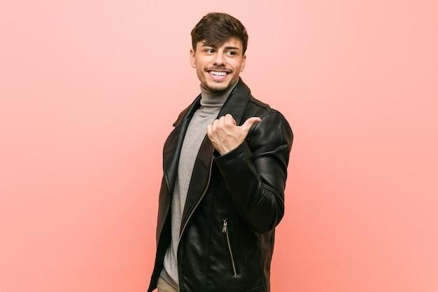 Jeune homme hispanique portant une veste en cuir pointe avec le pouce loin, riant et insouciant.