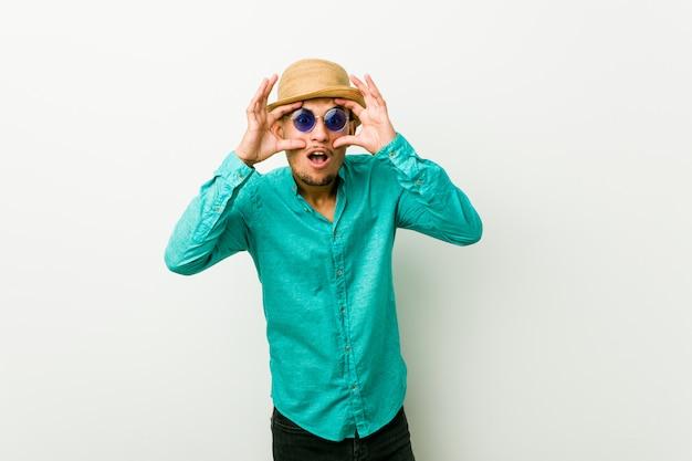 Jeune homme hispanique portant un vêtement d'été en gardant les yeux ouverts pour trouver une opportunité de réussite.