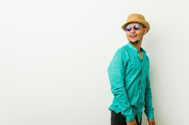 Jeune homme hispanique portant des vêtements d'été a l'air de côté souriant, joyeux et agréable.