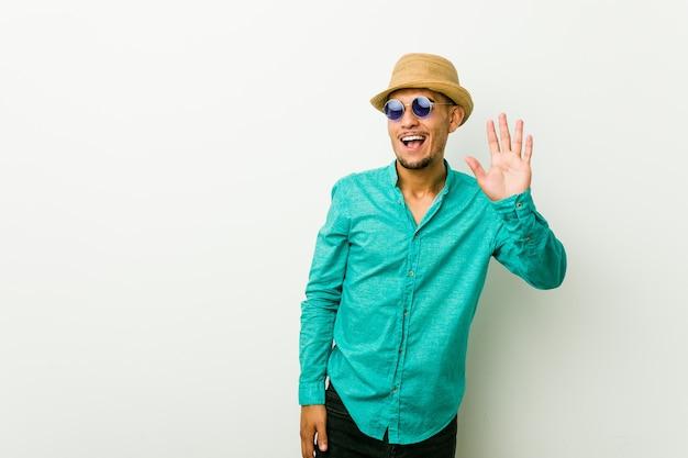 Jeune homme hispanique portant des vêtements d'été cligne un oeil et tient un bon geste avec la main.