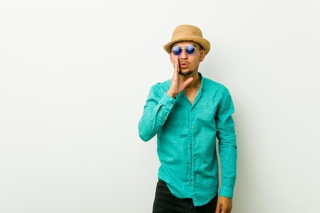 Jeune homme hispanique portant des vêtements d'été dit un secret chaud freinant les nouvelles et regardant de côté