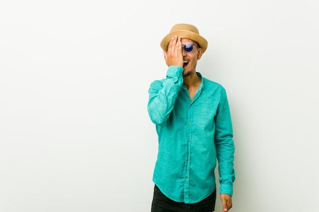 Jeune homme hispanique portant des vêtements d'été s'amusant couvrant la moitié du visage avec la paume.