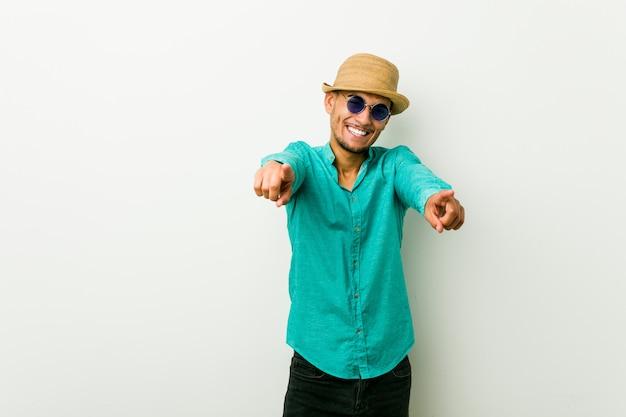 Jeune homme hispanique portant des vêtements d'été sourires joyeux pointant vers l'avant.