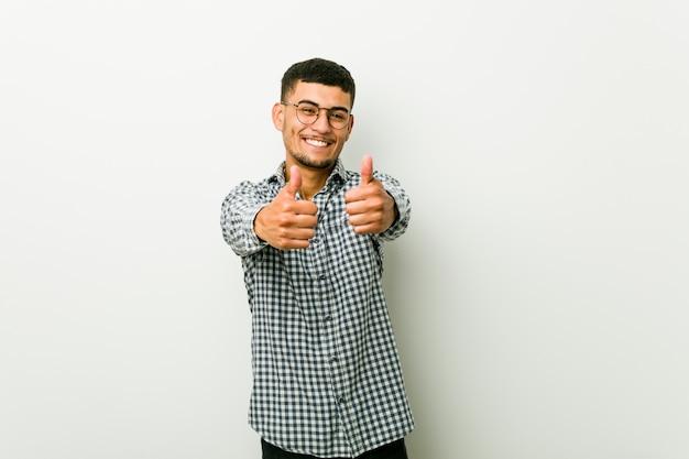 Jeune homme hispanique avec les pouces vers le haut, applaudit à quelque chose, soutient et respecte le concept.