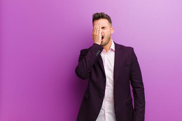 Jeune homme hispanique à la recherche de sommeil, s'ennuie et bâille, avec un mal de tête et une main couvrant la moitié du visage