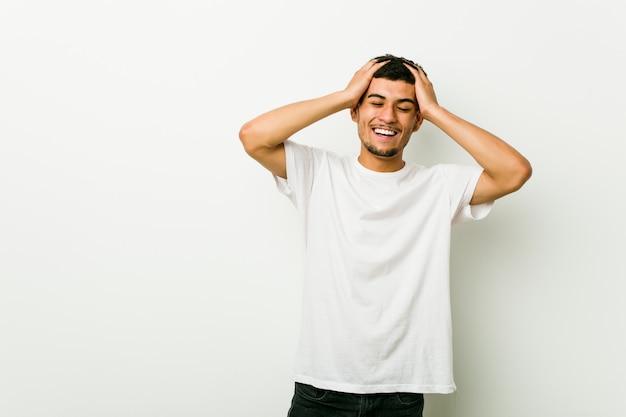 Jeune homme hispanique rit joyeusement en gardant les mains sur la tête. concept de bonheur.