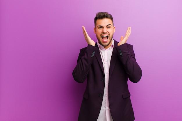 Jeune homme hispanique se sentant choqué et excité, en train de rire, étonné et heureux à cause d'une surprise inattendue