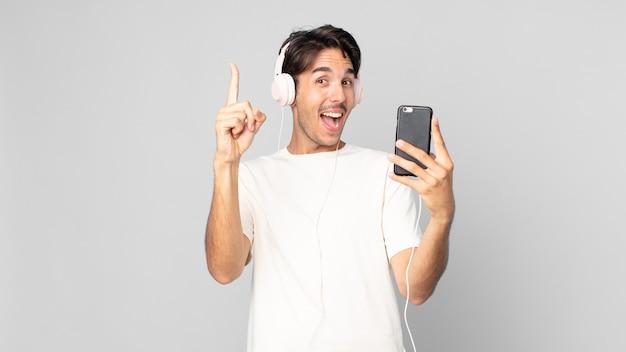 Jeune homme hispanique se sentant comme un génie heureux et excité après avoir réalisé une idée avec des écouteurs et un smartphone