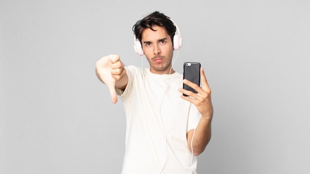 Jeune homme hispanique se sentant croisé, montrant les pouces vers le bas avec un casque et un smartphone