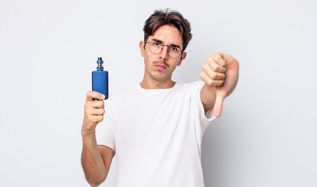 Jeune homme hispanique se sentant croisé, montrant les pouces vers le bas. concept de vaporisateur de fumée