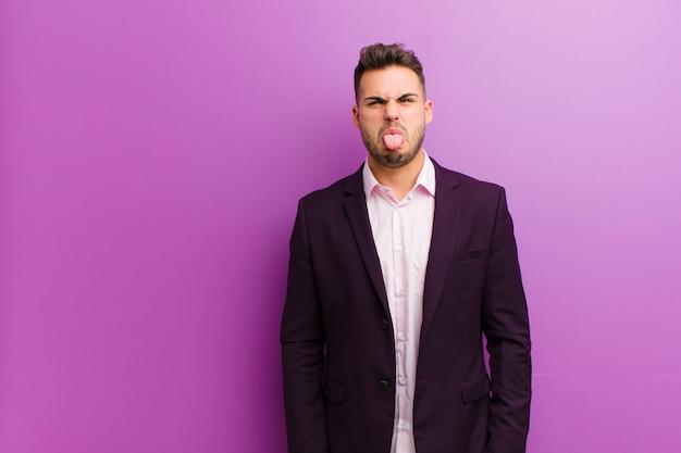 Jeune homme hispanique se sentant dégoûté et irrité, tirant la langue, n'aimant pas quelque chose de méchant et dégueulasse