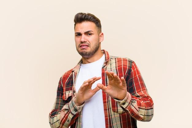 Jeune homme hispanique se sentant dégoûté et nauséeux, reculant de quelque chose de méchant, puant ou puant, disant beurk sur fond isolé