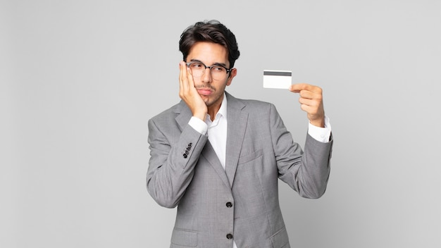 Jeune homme hispanique se sentant ennuyé, frustré et somnolent après une période fastidieuse et tenant une carte de crédit