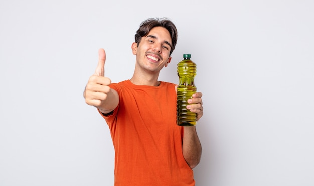Jeune homme hispanique se sentant fier, souriant positivement avec les pouces vers le haut. concept d'huile d'olive