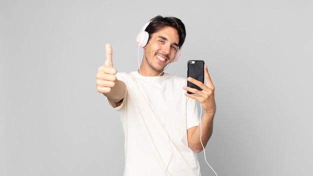 Jeune homme hispanique se sentant fier, souriant positivement avec les pouces vers le haut avec des écouteurs et un smartphone