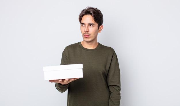Jeune homme hispanique se sentant triste, contrarié ou en colère et regardant sur le côté. concept de boîte blanche