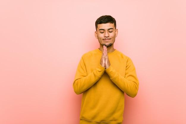 Jeune homme hispanique se tenant la main pour prier près de la bouche, se sent confiant.