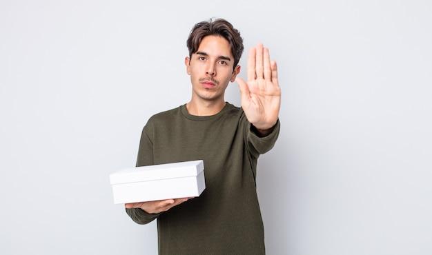 Jeune homme hispanique semblant sérieux montrant la paume ouverte faisant un geste d'arrêt. concept de boîte blanche