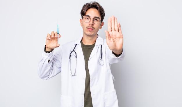 Jeune homme hispanique semblant sérieux montrant la paume ouverte faisant un geste d'arrêt. concept de seringue de médecin