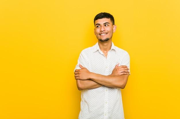 Jeune homme hispanique souriant confiant avec les bras croisés.