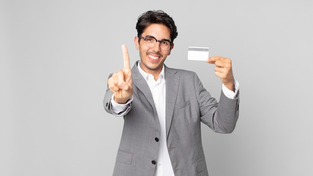 Jeune homme hispanique souriant fièrement et avec confiance faisant le numéro un et tenant une carte de crédit