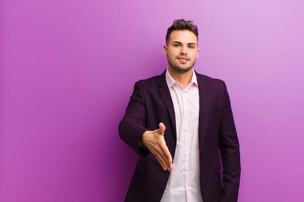 Jeune homme hispanique souriant, heureux, confiant et amical, offrant une poignée de main pour conclure un marché, coopérant